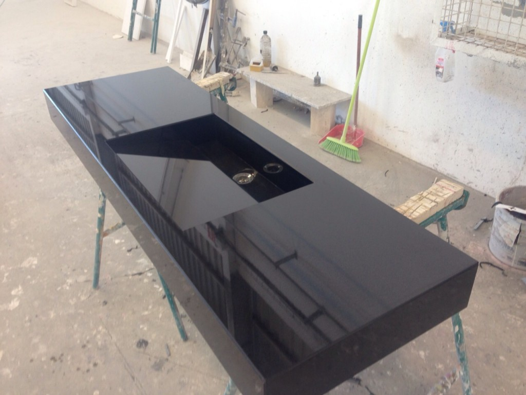 Encimera de granito negro intenso de 12 cm de alto con fregadero inclinado.